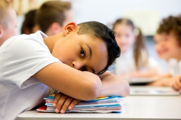 child with head on desk, growth mindset activities for kids and adults