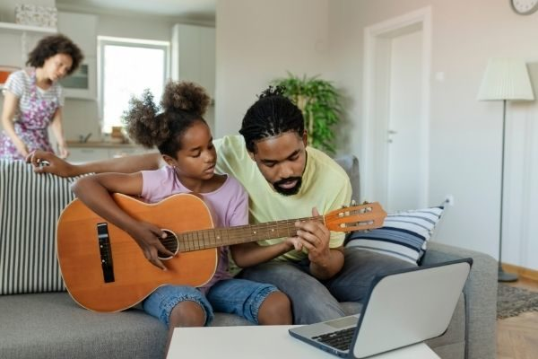 dad teaching daughter guitar, hands-on growth mindset for kids