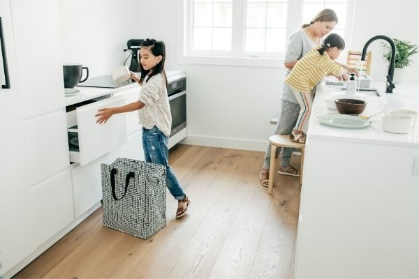girl doing laundry with her morning checklist for kids