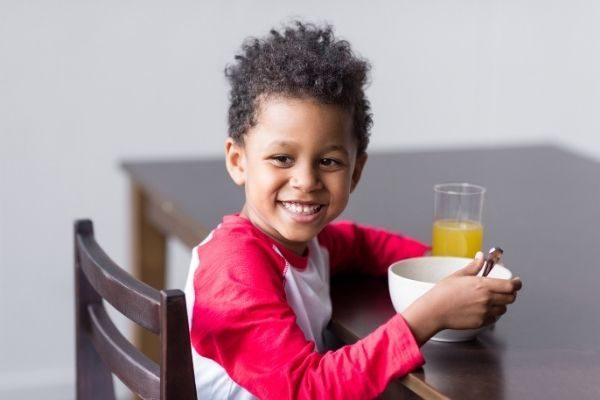 child eating breakfast following his kids morning routine chart