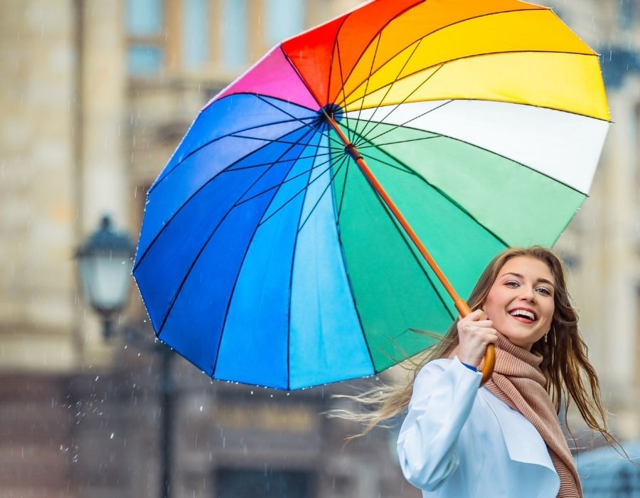 woman with umbrella doing one of the awesome 30 day happiness challenges