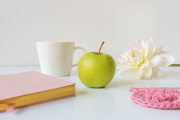 What is a good self care sunday routine: apple, book, flowers photo