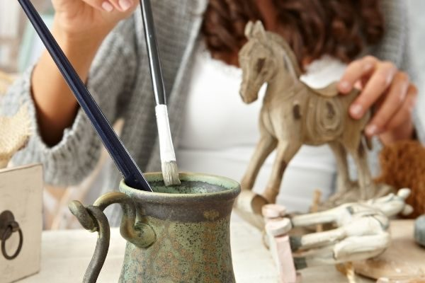 a woman painting a horse
